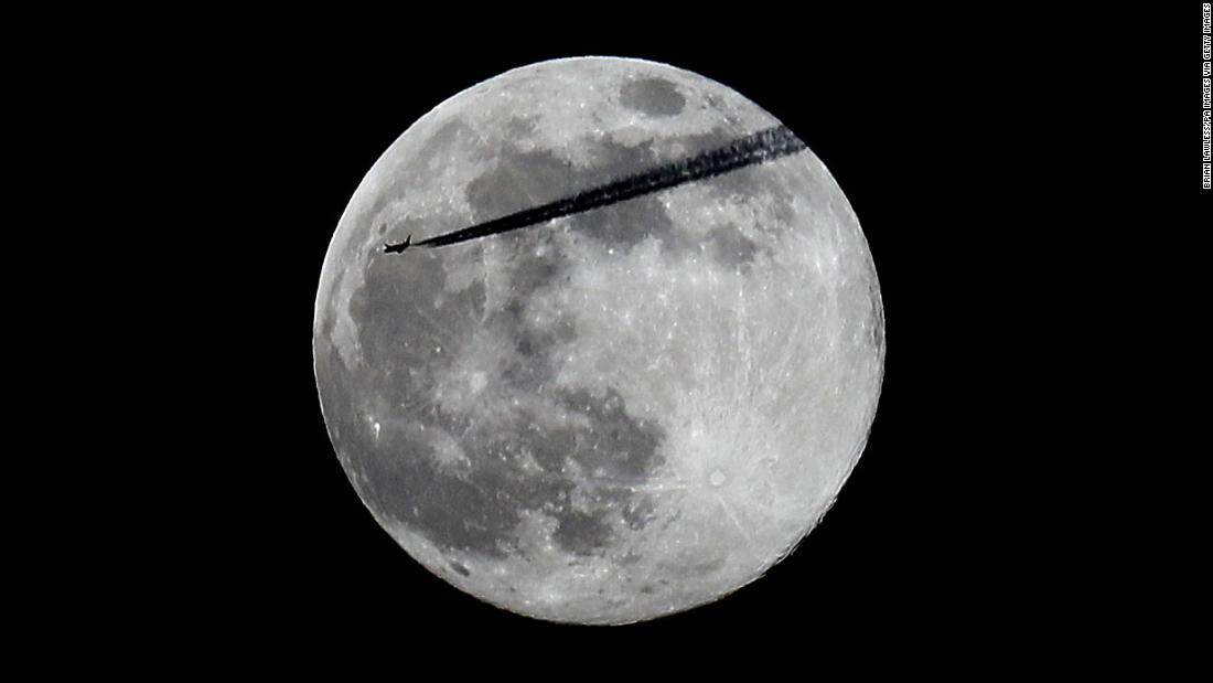 A plane passes the pink supermoon as it rises over Dublin, Ireland.