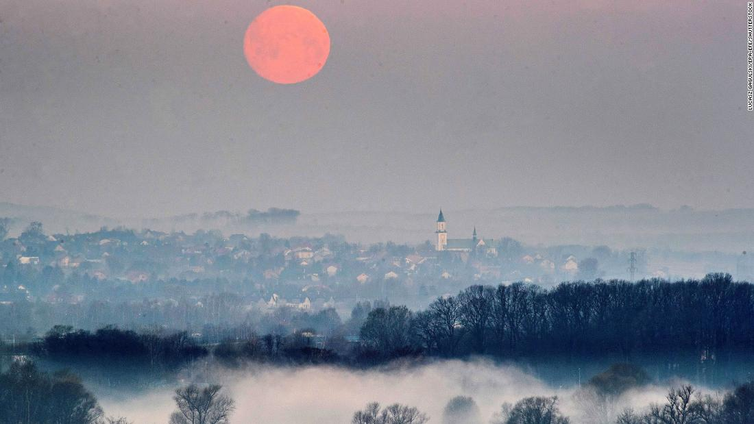 The moon takes on a reddish hue as it reflects the light of early dawn in Krakow, southern Poland.