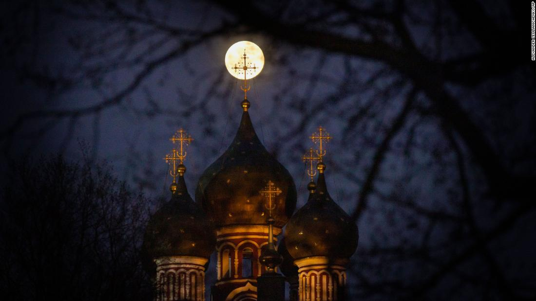 The supermoon rises behind an illuminated cross from an Orthodox church in Moscow.