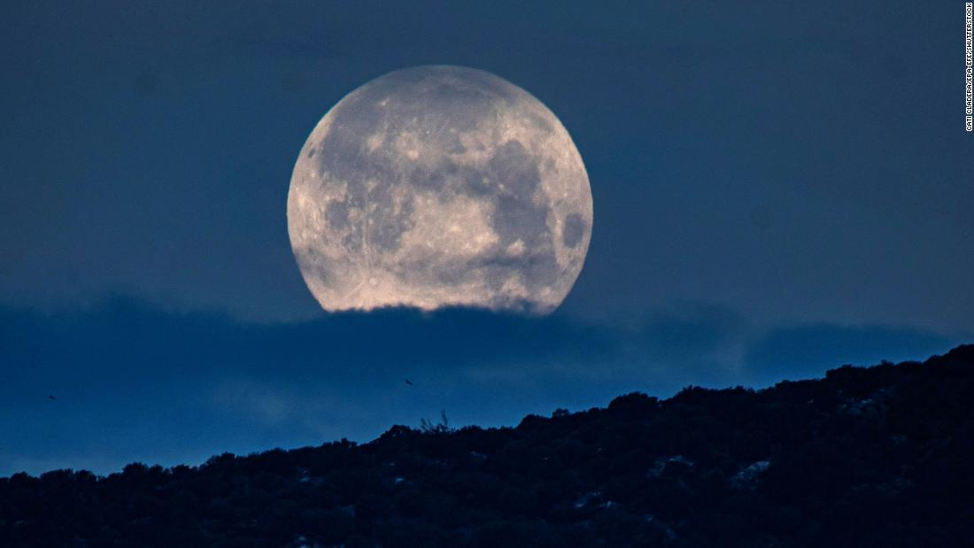 The pink supermoon is seen above San Telmo in Spain's Balearic Islands in the early hours of April 8.