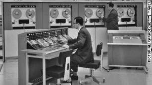Two men operating a mainframe computer, circa 1960.