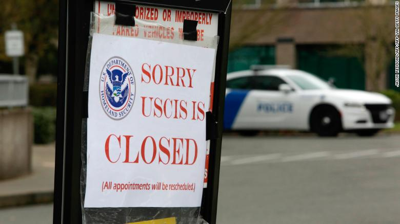 A sign showing the closure of a US Citizenship and Immigration Services (USCIS) field office in Washington. Immigrants in the US have faced uncertainty over their work visas due to the coronavirus crisis.