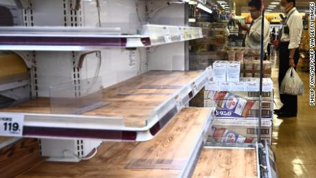 People shop near empty food shelves at a supermarket in Tokyo in April 6, 2020. - Japan's Prime Minister Shinzo Abe said on April 6 the government plans to declare a state of emergency and proposed a stimulus package worth 1 trillion USD as new coronavirus infections spike in Tokyo and elsewhere. (Photo by Philip FONG / AFP) (Photo by PHILIP FONG/AFP via Getty Images)