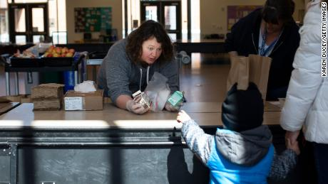 SEATTLE, WA - MARCH 18: Christy Cusick hands out free school lunches to kids and their parents at Olympic Hills Elementary School on March 18, 2020 in Seattle, Washington. As a result of all schools in Washington state being closed due to the COVID-19 outbreak until at least April 27th, Seattle Public Schools is providing carry-out meals to students during lunch hours. (Photo by Karen Ducey/Getty Images)