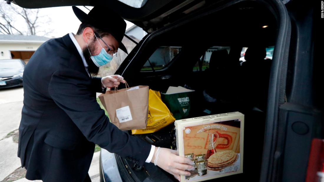 Rabbi Yaakov Kotlarsky places Passover Seder to-go packages into a car trunk in Arlington Heights, Illinois, on April 7.