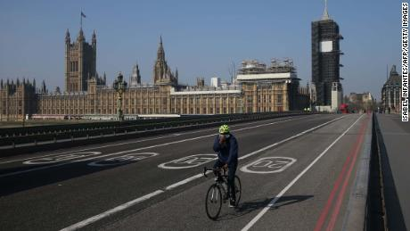 "A cyclist crosses a near-empty Westminster Bridge with the Houses of Parliament in the background in central London on April 9, 2020. - British Prime Minister Boris Johnson on Thursday began a fourth day in intensive care ""improving"" in his battle with coronavirus, as his government prepared to extend a nationwide lockdown introduced last month. (Photo by ISABEL INFANTES / AFP) (Photo by ISABEL INFANTES/AFP via Getty Images)"