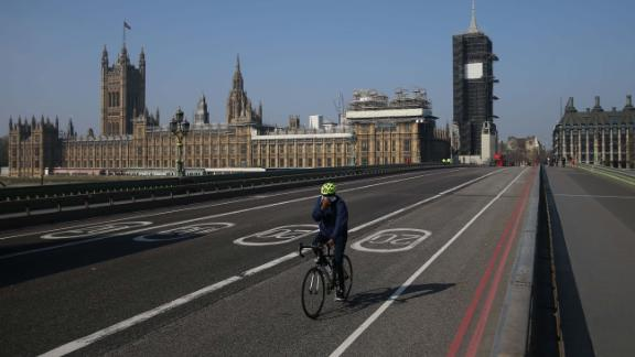 """A cyclist crosses a near-empty Westminster Bridge with the Houses of Parliament in the background in central London on April 9, 2020. - British Prime Minister Boris Johnson on Thursday began a fourth day in intensive care """"improving"""" in his battle with coronavirus, as his government prepared to extend a nationwide lockdown introduced last month. (Photo by ISABEL INFANTES / AFP) (Photo by ISABEL INFANTES/AFP via Getty Images)"""
