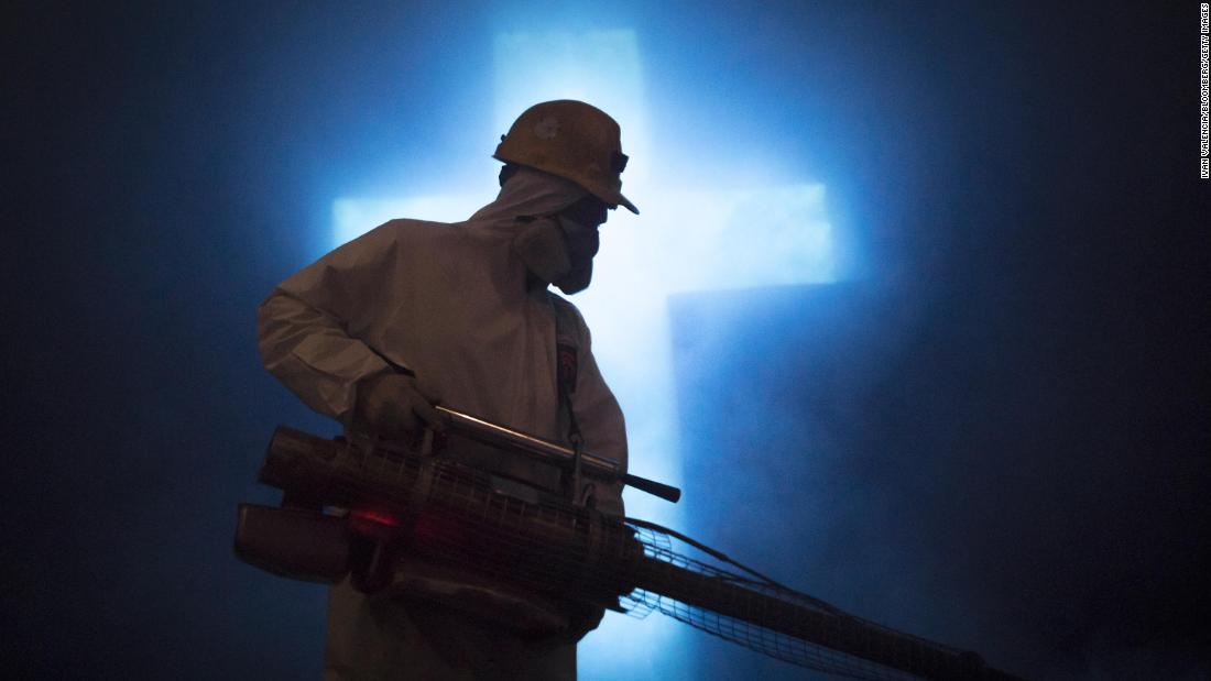 A worker disinfects a carved cross at the Salt Cathedral in Zipaquira, Colombia, on April 8, 2020.