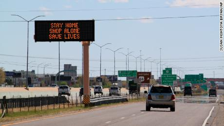 Flashing highway message boards along Interstate 25 in Albuquerque, New Mexico, on April 9 urge people in both English and Spanish to stay home amid the coronavirus outbreak.