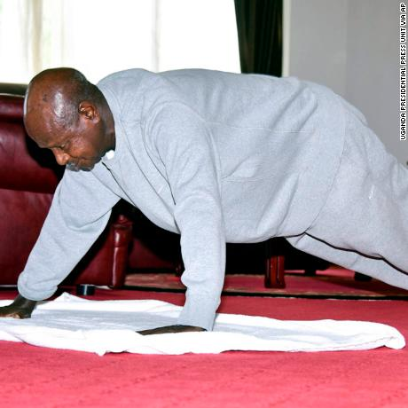 In this handout photo provided by Uganda's Presidential Press Unit, Uganda's President Yoweri Museveni performs push-ups in a video released to the public via the president's social media accounts, at State House in Entebbe, Uganda Thursday, April 9, 2020. Uganda's 75-year-old president has released a homemade exercise video to show skeptical countrymen that one can stay in shape under the lockdown that has been implemented to curb transmission of the new coronavirus. (Uganda Presidential Press Unit via AP)