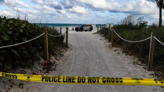 """Miami Police patrol at the closed Miami Beach in Miami, on March 19, 2020. - The Miami Beach mayor, Dan Gelber, warned of """"devastating consequences"""" over the virus and ordered bars and gyms to close this week, telling springbreakers: """"You've got to think about the person next to you and even the person you don't know."""""""