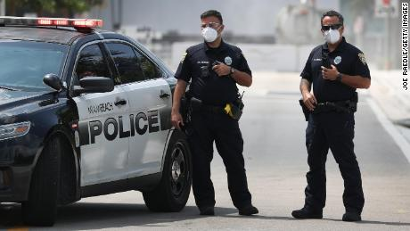 Miami Beach police officers wear protective masks.