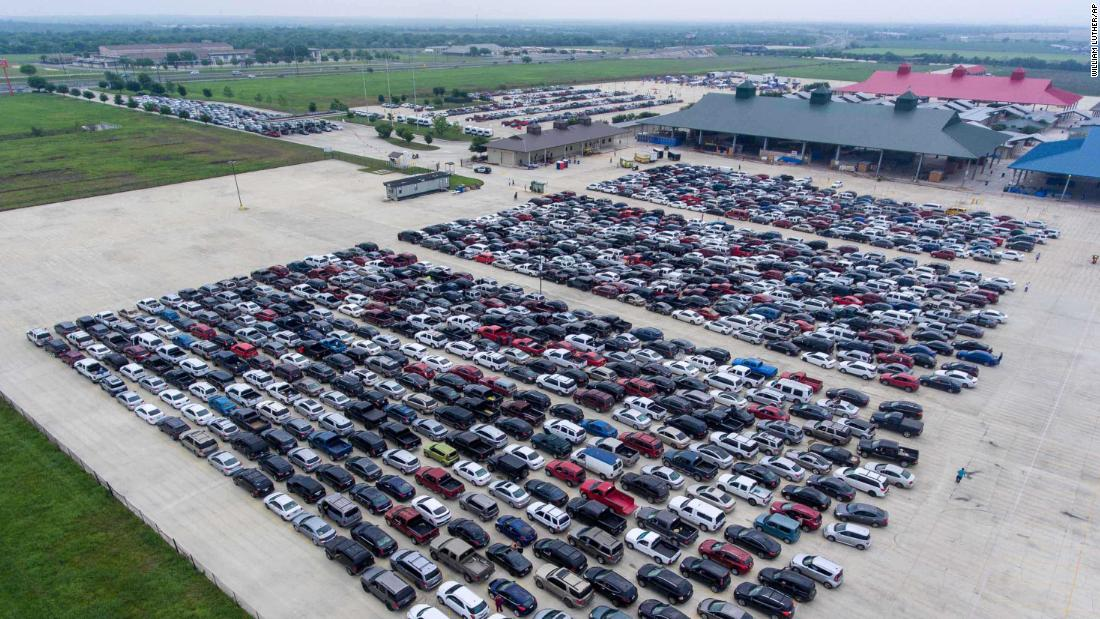 People wait in their cars for the San Antonio Food Bank to begin food distribution on April 9, 2020.