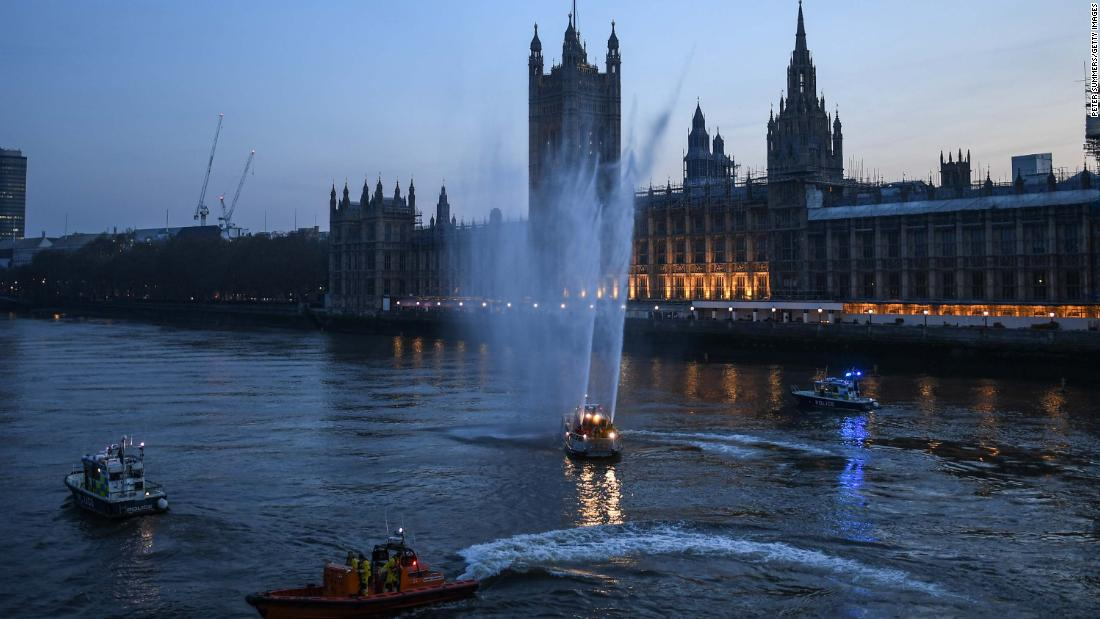 Service boats spray water in London to show support for health care workers on April 9, 2020.