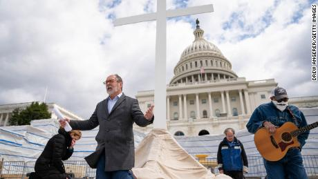 Rev. Patrick Mahoney, director of the Christian Defense Coalition, kneels in prayer as he livestreams a Good Friday service on the grounds of the U.S. Capitol on April 10, 2020, in Washington, DC.