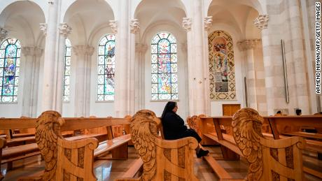 A nun sits among empty pews at the Good Friday celebration at the Mother Teresa cathedral on April 10, 2020, in Pristina, Kosovo.