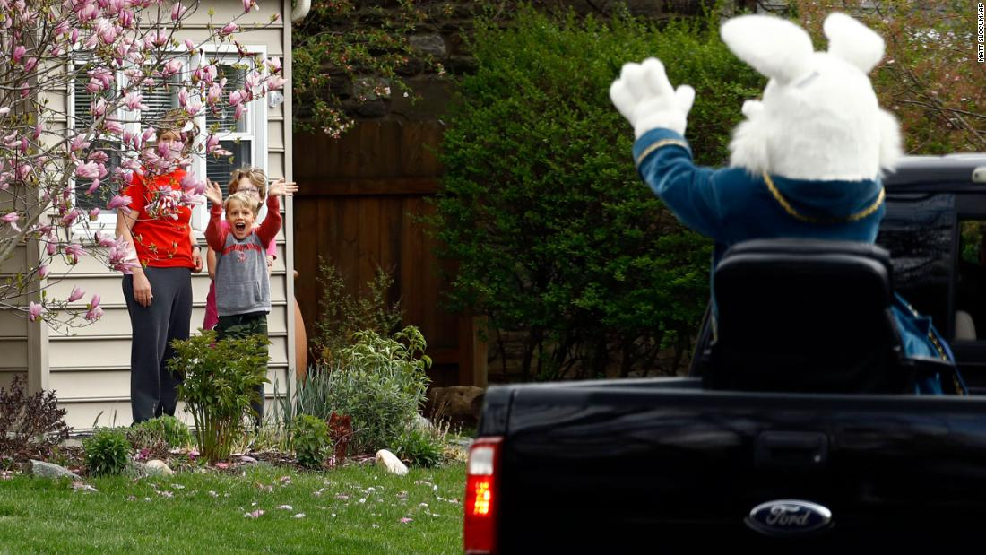Children wave to a person dressed as the Easter Bunny during a neighborhood parade in Haverford, Pennsylvania, on April 10, 2020.