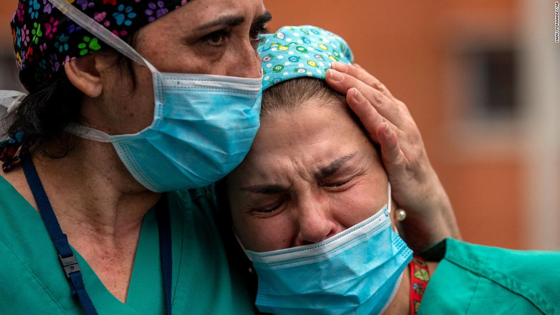 Health workers in Leganes, Spain, cry during a memorial for a co-worker who died because of the coronavirus.
