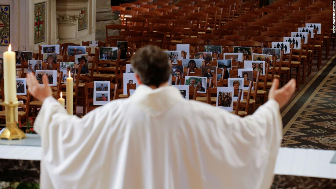 Priest Xavier Lemble holds an Easter mass with photos of parishioners in the pews in Bethune, France, on April 12.