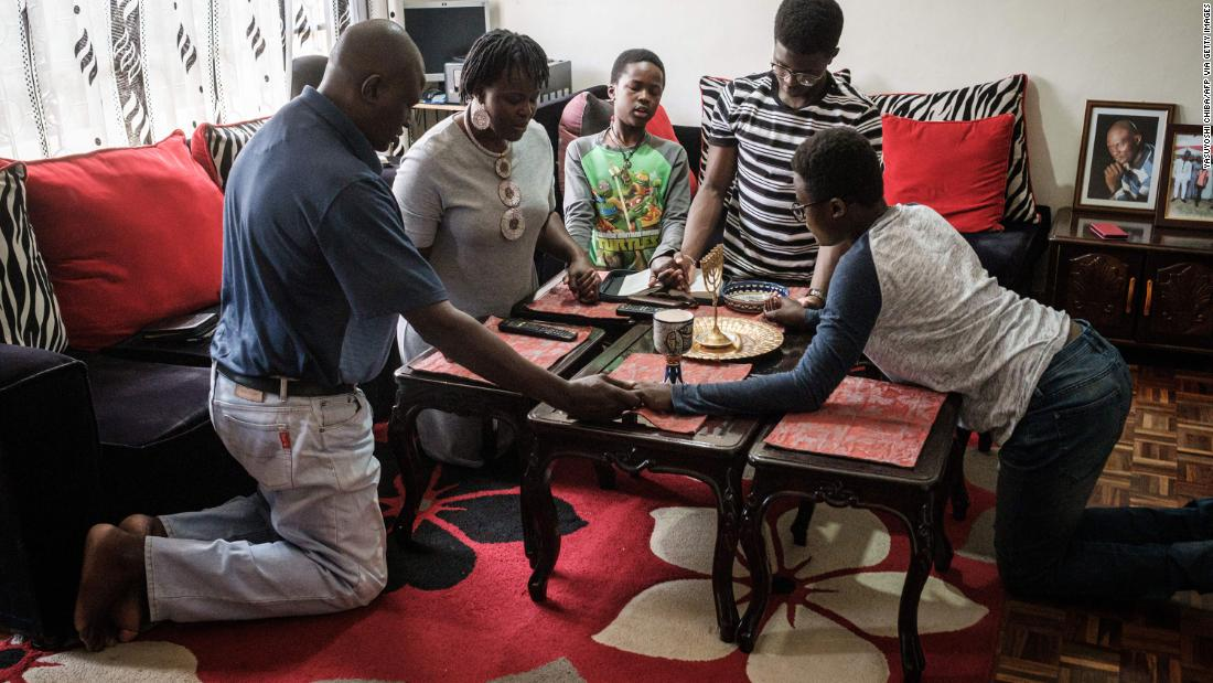 A family prays together at home as they follow the live broadcast of an Easter Sunday service on television from the All Saints' Cathedral in Nairobi, Kenya.