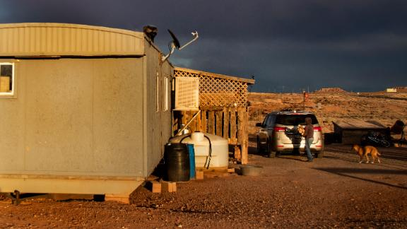 A Navajo woman carries wood to heat her rural mobile home during the coronavirus pandemic on March 27, 2020, in Cameron, Arizona.