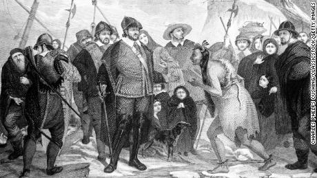 An illustration of Myles Standish and Pilgrims greeting a Native American at Plymouth Rock in 1620.