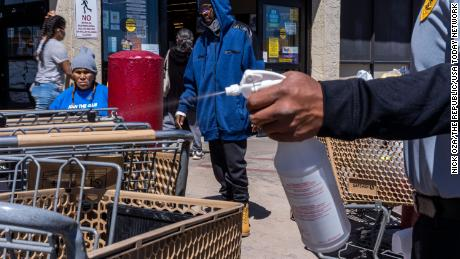 A Safeway security guard sprays bleach on a shopping cart on April 11, 2020, in Winslow, Arizona, where Navajos go to stock up on food and seek medical help.
