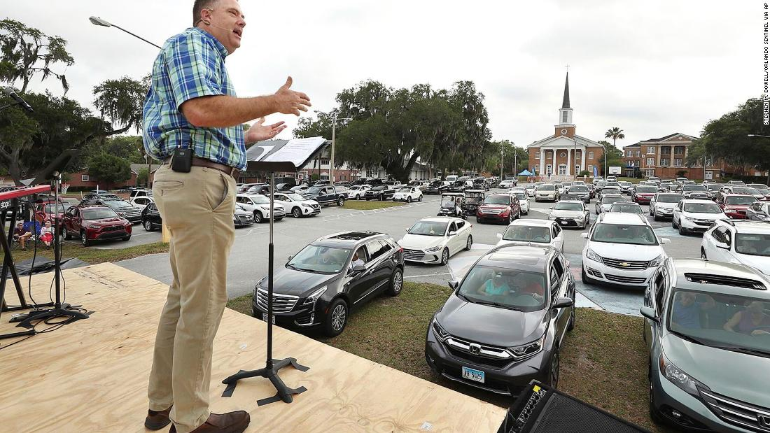 Pastor Cliff Lea preaches over a parking lot filled with cars during a drive-in service at the First Baptist Church of Leesburg, Florida.
