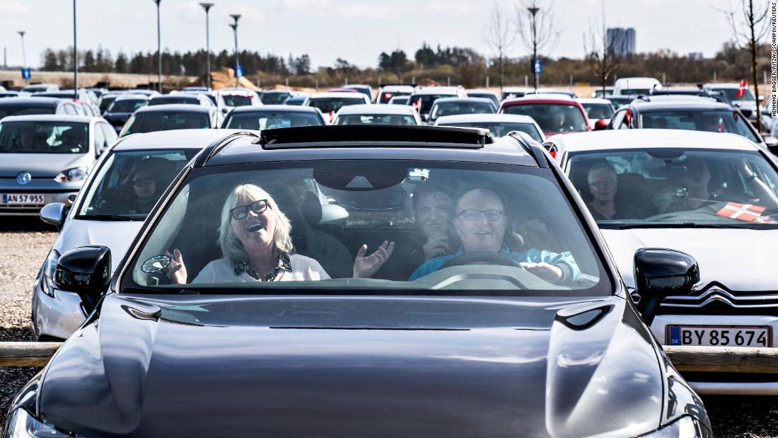 People sing hymns in their cars in a parking lot at the Aalborg Airport in Denmark.