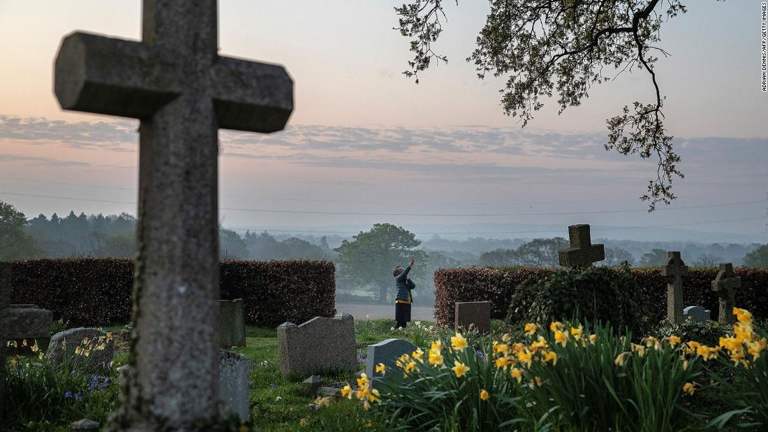 Priest-in-charge Angie Smith uses her phone to broadcast an Easter service from a churchyard in Hartley Wintney, England, on April 12.