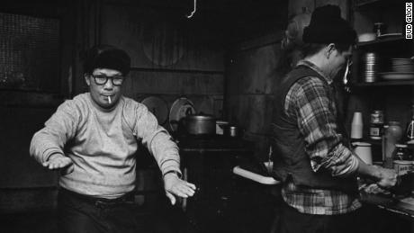 Two men, one smoking, one cooking, in their apartment on Bayard Street in Manhattan's Chinatown, circa 1979-1984.
