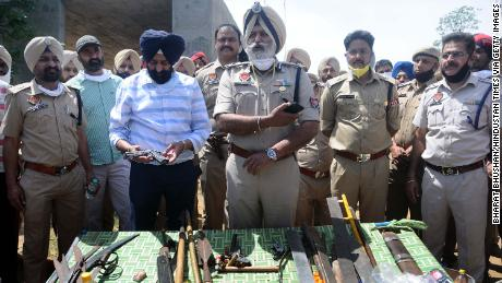 Police officers show sharp-edged weapons recovered in Patiala, India, on April 12.