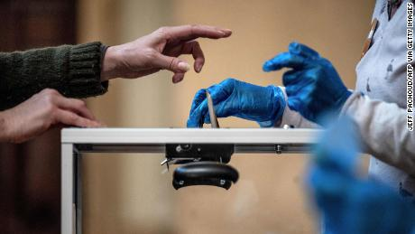 A voter casts their ballot in front of an official wearing plastic gloves in a polling station of Lyon on March 15, 2020 during the first round of the mayoral elections.