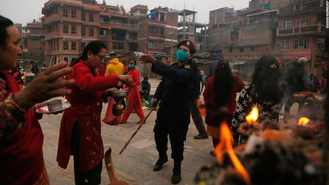 A police officer requests that people return to return to their homes during a gathering that marked the Bisket Jatra festival in Bhaktapur, Nepal.