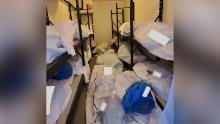 Body bags and blue bags containing the personal effects of the deceased are seen piled inside a portable refrigerator storage unit outside the hospital.