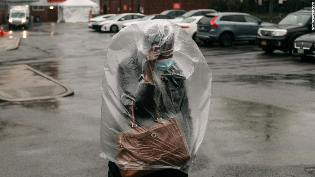 A woman covers herself with plastic as heavy rain falls outside a New York hospital on April 13, 2020.