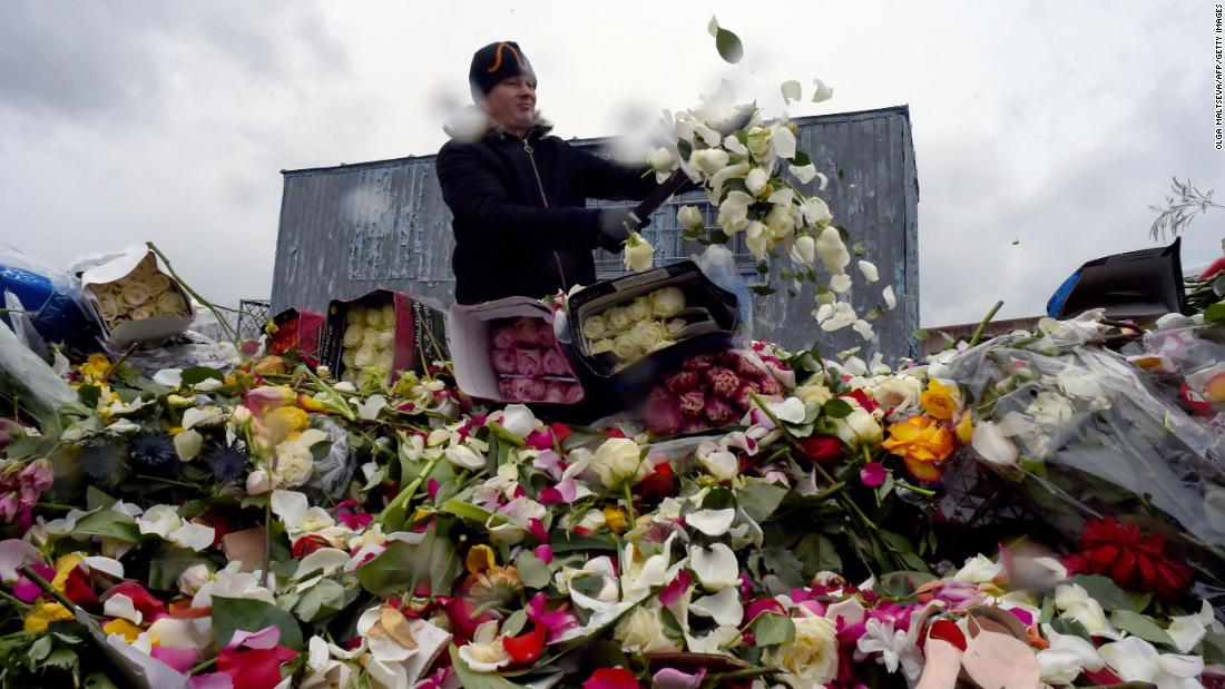 A flower shop employee destroys unsold flowers in St. Petersburg, Russia, on April 13, 2020.