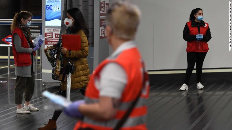 Spanish Red Cross volunteers distribute face masks at the Chamartin Station in Madrid on April 13.