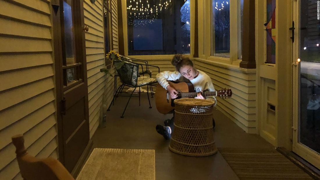 Steve Schneider's 18-year-old daughter plays her guitar on their porch in Sheboygan, Wisconsin