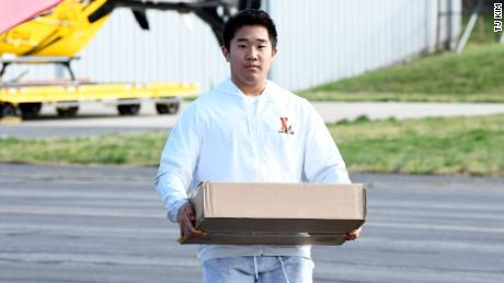 Kim carries essential supplies to his plane. He hopes to attend the US Naval Academy after high school.