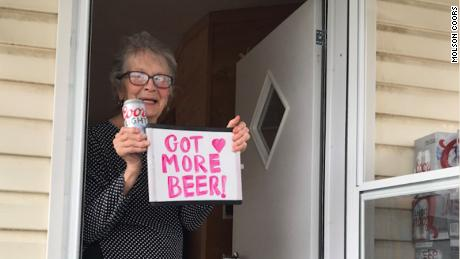 The 93-year-old stands on her porch with her Coors Light delivery.