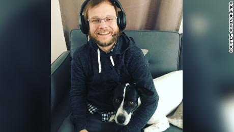"""Trevor Andrews, a violist and """"Apex Legends"""" video game coach, poses with his dog, Charlie, in April 2019."""