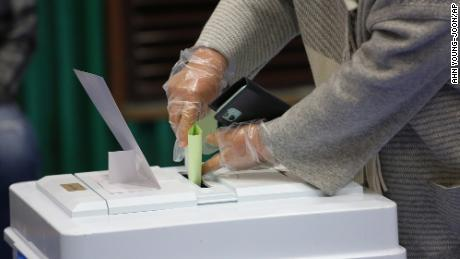 A voter wearing plastic gloves to help protect against the spread of coronavirus casts a vote for the parliamentary election at a polling station in Seoul.