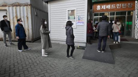 South Koreans wait in line to cast their ballots for the parliamentary elections at a polling station in Seoul.
