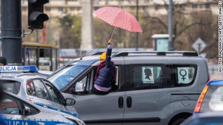 Women protest from their cars with umbrellas, a symbol of the abortion rights movement.
