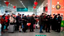 Passengers in face masks queueing to show a green QR code on their phones to security upon arrival at Wenzhou railway station in Wenzhou.