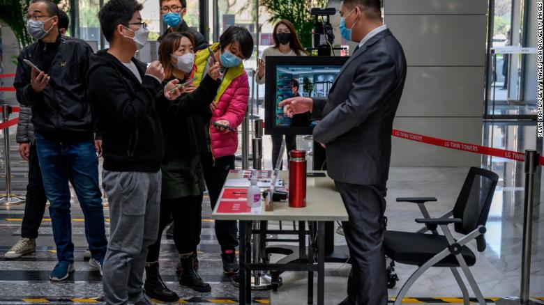 Chinese office workers show their mobile phones with their health code to a guard, which shows they have permission to travel and are virus free, as they arrive at an office building on April 10.
