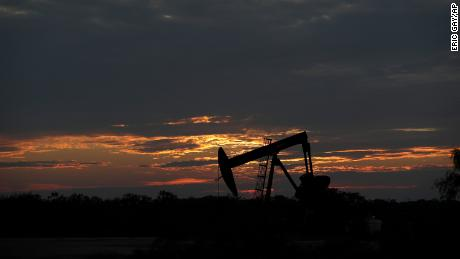 The sun sets behind an idle pump jack near Karnes City, Texas, Wednesday, April 8, 2020. Demand for oil continues to fall due to the new coronavirus outbreak. (AP Photo/Eric Gay)