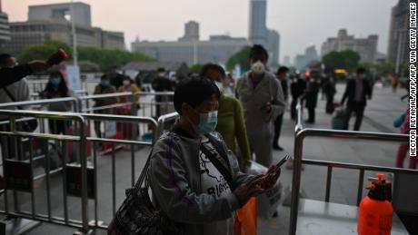 Passengers check their Wuhan Health code in front of the Hankou Train Station in Wuhan on April 8.