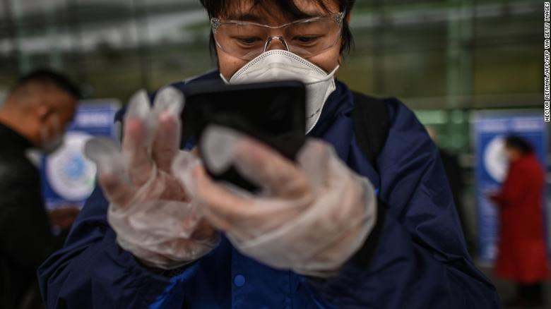 A passenger uses a smartphone while scanning a Wuhan city health QR code before entering Tianhe Airport in Wuhan on April 11.